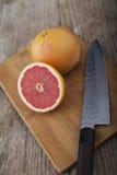 木表面上的葡萄柚与刀子 免版税库存图片