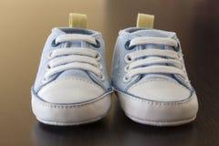 木表面上的蓝色婴儿运动鞋 免版税库存照片