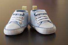 木表面上的蓝色婴儿运动鞋 免版税库存图片