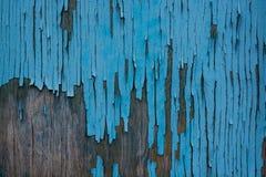 木表面上的蓝色破裂的绘画 库存图片