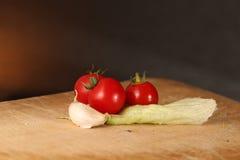 木表面上的蕃茄大蒜和莴苣 库存照片
