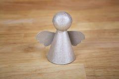 木表面上的银色天使 库存图片