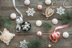 木表面上计划的圣诞节装饰 冷杉分支、桃红色/银丝带和球,白色蛋白软糖,雪花,玩具鹿a 免版税库存照片