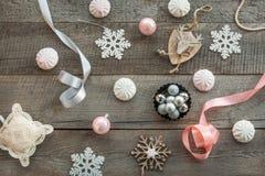 木表面上计划的圣诞节装饰 冷杉分支、桃红色/银丝带和球,白色蛋白软糖,雪花,玩具鹿a 库存照片
