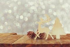 木装饰圣诞树、驯鹿和杉木锥体的抽象图象在木桌和圣诞节假日bokeh光上的 免版税图库摄影