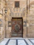 木装饰的铜在阿尔苏丹Barquq清真寺镀了门和石头砖墙,老开罗,埃及庭院  库存照片