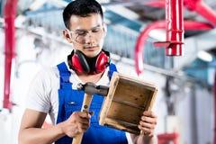 木车间工作的亚裔木匠 库存图片
