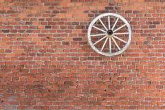 木轮子在砖墙上垂悬 免版税库存照片