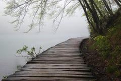 木道路在有有薄雾的雾的Plitvice湖 免版税库存图片