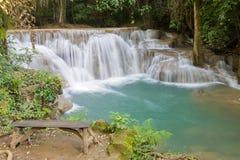 木长凳和瀑布在热带深森林里 免版税库存照片