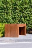 木长凳在有小绿色树的庭院里在背景中 库存图片