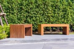 木长凳在有小绿色树的庭院里在背景中 免版税图库摄影