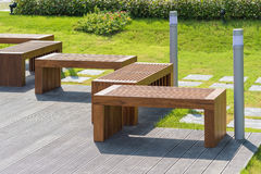 木长凳在有小绿色树的庭院里在背景中 库存照片