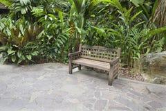 木长凳在热带庭院里 图库摄影