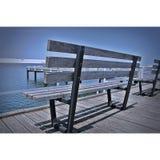 木长凳湖边 免版税库存图片