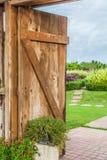 木门开放有草甸和蓝天的后面看法 免版税库存照片