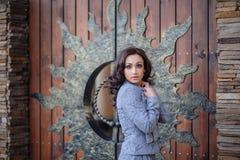 木门背景的美丽的女孩  免版税图库摄影