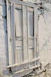 木门绘了在用落盖的石墙壁的白色膏药 免版税库存照片