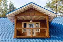 木阳台在有蓝色屋顶的一个小屋里 免版税库存图片