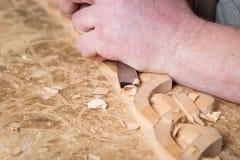 木雕家创造一件家具装饰品 木雕家` s手,凿子,工具,木头雕刻了装饰品 免版税库存照片