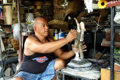 木雕刻师在一个装饰小雕象投入最后一笔被卖在Dapitan拱廊在马尼拉,菲律宾 库存照片