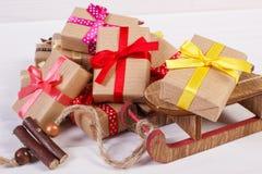 木雪撬和被包裹的礼物与五颜六色的丝带圣诞节或其他庆祝的 免版税库存照片