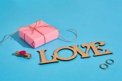 木题字爱、礼物盒和圆环在蓝色背景 花束金刚石订婚结婚提议环形玫瑰 华伦泰` s天的概念 免版税库存照片