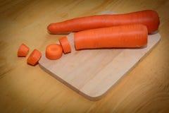 木头投入了晚餐的大红萝卜 库存图片