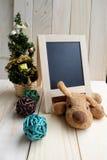 木黑板和圣诞节装饰与被充塞的狗 免版税图库摄影