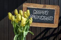 木黑板生日快乐标志美丽的黄色郁金香用桶提春天花郁金香褐色背景 库存照片