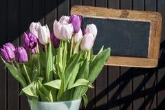 木黑板copyspace标志美丽的桃红色郁金香用桶提春天花郁金香褐色背景 免版税库存图片