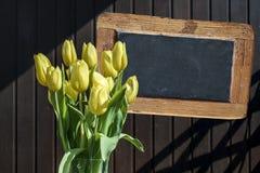 木黑板copyspace标志美丽的黄色郁金香用桶提春天花郁金香褐色背景 图库摄影