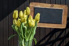 木黑板copyspace标志美丽的黄色郁金香用桶提春天花郁金香褐色背景 免版税库存图片