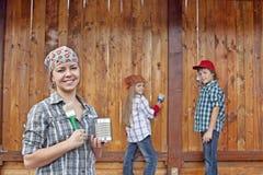 绘木头棚子的妇女和孩子 免版税库存照片