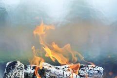 木头燃烧的被烧焦的日志与红色火焰和烟的 免版税库存图片