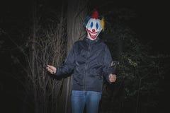 木头的可怕小丑与刀子和轴 库存照片