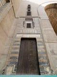 木年迈的墙壁、木门和镶边的黑白大理石装饰 免版税库存图片