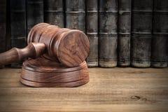 木Jydges惊堂木和老法律书籍在木背景 免版税库存图片