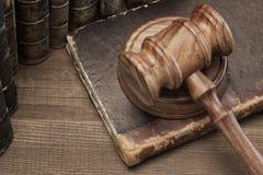 木Jydges惊堂木和老法律书籍在木表上 图库摄影