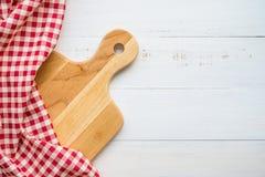 未使用的全新的棕色手工制造木切板和红色餐巾顶视图在白色木桌背景-食物和kitch 免版税图库摄影