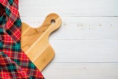 未使用的全新的棕色手工制造木切板和红色餐巾顶视图在白色木桌背景-食物和kitch 免版税库存照片