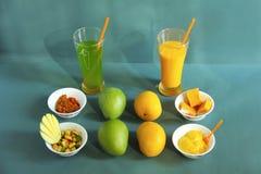 未加工和成熟亚尔方索芒果和他们的副产物喜欢腌汁、芒果震动、甜点和冰淇凌 库存照片