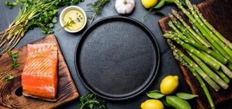 未加工的三文鱼内圆角、芦笋、柠檬和草本在生铁板材附近 烹调与拷贝空间的食物背景 顶视图 免版税库存图片