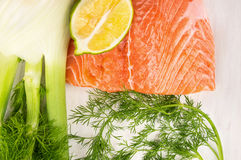 未加工的三文鱼内圆角、莳萝、茴香和柠檬在白色桌上 免版税库存图片