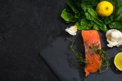 未加工的三文鱼内圆角用麝香草、大蒜、柠檬和菠菜在dar 库存图片