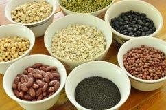 未加工的品种豆和谷物植物杯子的在木桌上 库存图片