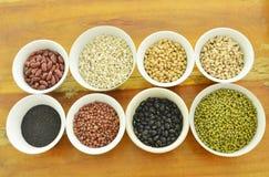 未加工的品种豆和谷物植物杯子的在木桌上 图库摄影