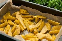 未加工的土豆油煎在烘烤纸和绿色的切片 图库摄影