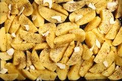 未加工的土豆用准备好的香料被烤 免版税库存照片