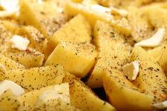 未加工的土豆用准备好的香料被烤 免版税库存图片